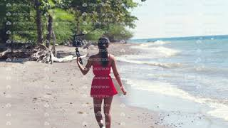 Millennial female vlogger filming travel and vacation vlog at the beach.