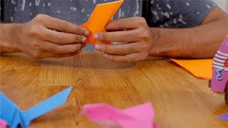 Close up shots of a boy's hands folding origami from orange paper