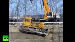 Video: Bulldozer and 35-ton crane topple into pit at Russian construction site