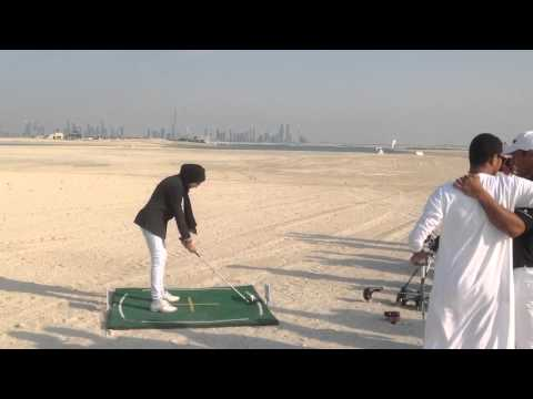 UAE female golfer hitting some balls on the World Islands in Dubai.