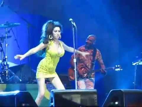 Amy Winehouse faz pirueta e cai no palco durante show