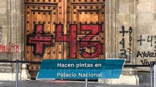 Mientras padres de los 43 normalistas de Ayotzinapa realizaban un mitin en el Zócalo, un grupo de jóvenes brincó las vallas que rodean Palacio Nacional e hicieron pintas en la puerta mariana y el edificio