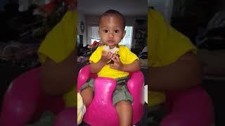 Baby eats Panera Bread roll in Bruce Lee onesie