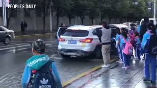 #HeartwarmingMoment: Car driver parked by the curb to help students cross rain puddle.