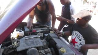 Rev. Harris Teaching African American Youth How To ID Different Parts On A Car Motor.