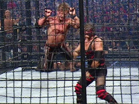 Kane throws Chris Jericho through the glass pod of