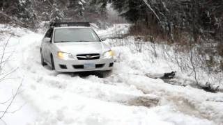 White Subaru Legacy on snow