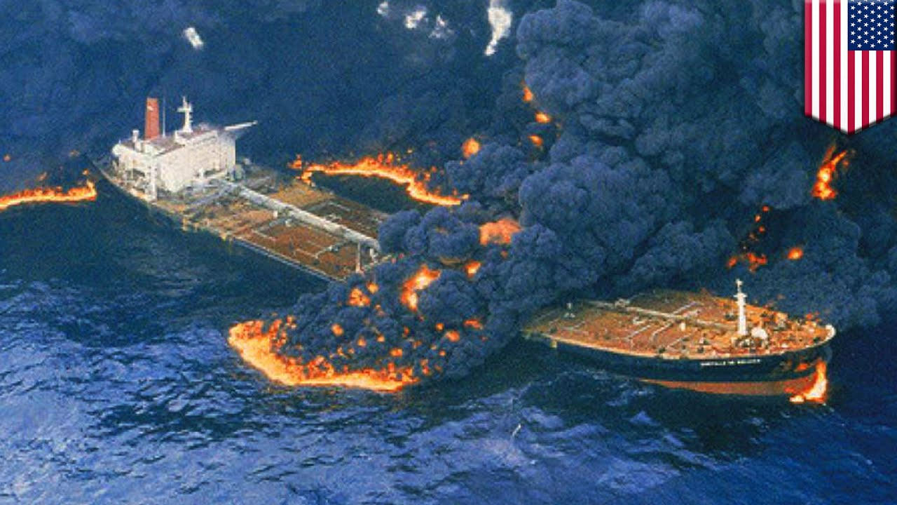 A burning oil tanker with flaming oi spilling into the sea