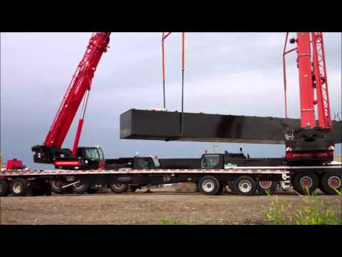 TWO CRANES UNLOAD A 60 FT LONG METAL TANK
