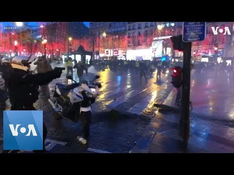 French Policeman Pulls Gun On Protesters on Champs Elysees