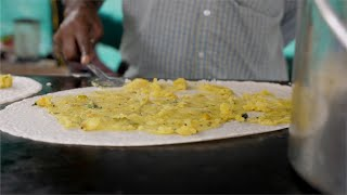A road side food stall owner preparing masala dosa and adding mashed potatoes on the dosa batter