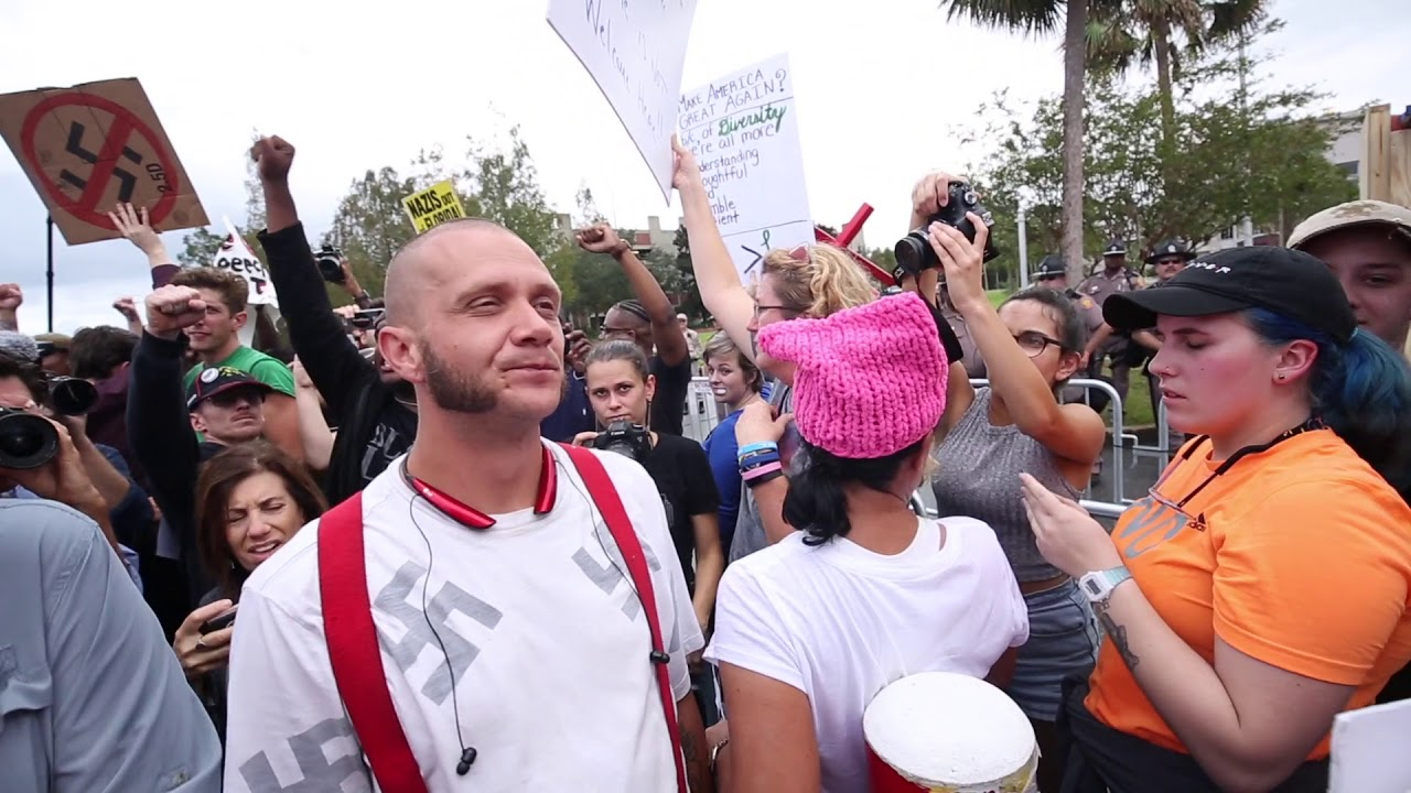 Download Swastika-wearer walks amid protesters, gets punched