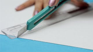 Close shot of girls hand cutting a sheet of cutting cardboard paper with knife