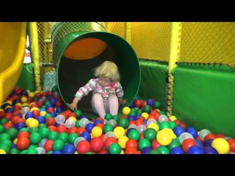 Лиза играет, прыгает на батуте, катается с горки в сухой бассейн с шариками. Детский лабиринт.