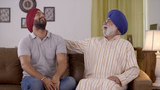 Indian father and son having a good laugh at home sitting on the couch - Happy family spending time together