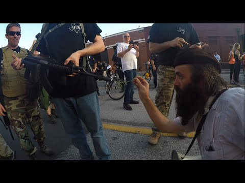 Protester puts flower in the barrel of a gun at Trump (*Unable to correct  Islamophobic belief)