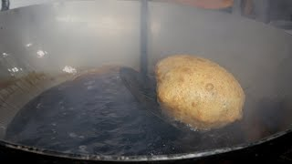 Deep frying a bhatura in a large kadhai/wok