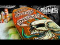 Painting a surfboard with a tattoo-style screaming skull design using spray paint and paint markers