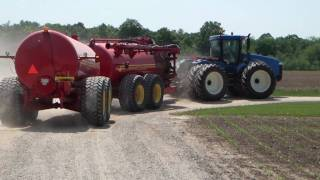New Holland Articulating Tractor Spreading Manure with a Nuhn Quad Train