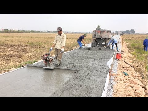 Construction A Concrete Road Stretching On Rural Fields With Ready-Mixed Concrete