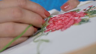 Closeup shot of Indian women/female/girl is embroidering cross stitch on the fabric