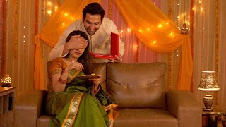 Caring husband giving a surprise gift to lovable wife on Diwali - Decorated house with colorful background