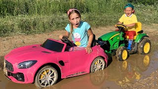 Sofia stuck in the mud Max ride on Power Wheels Tractor to help