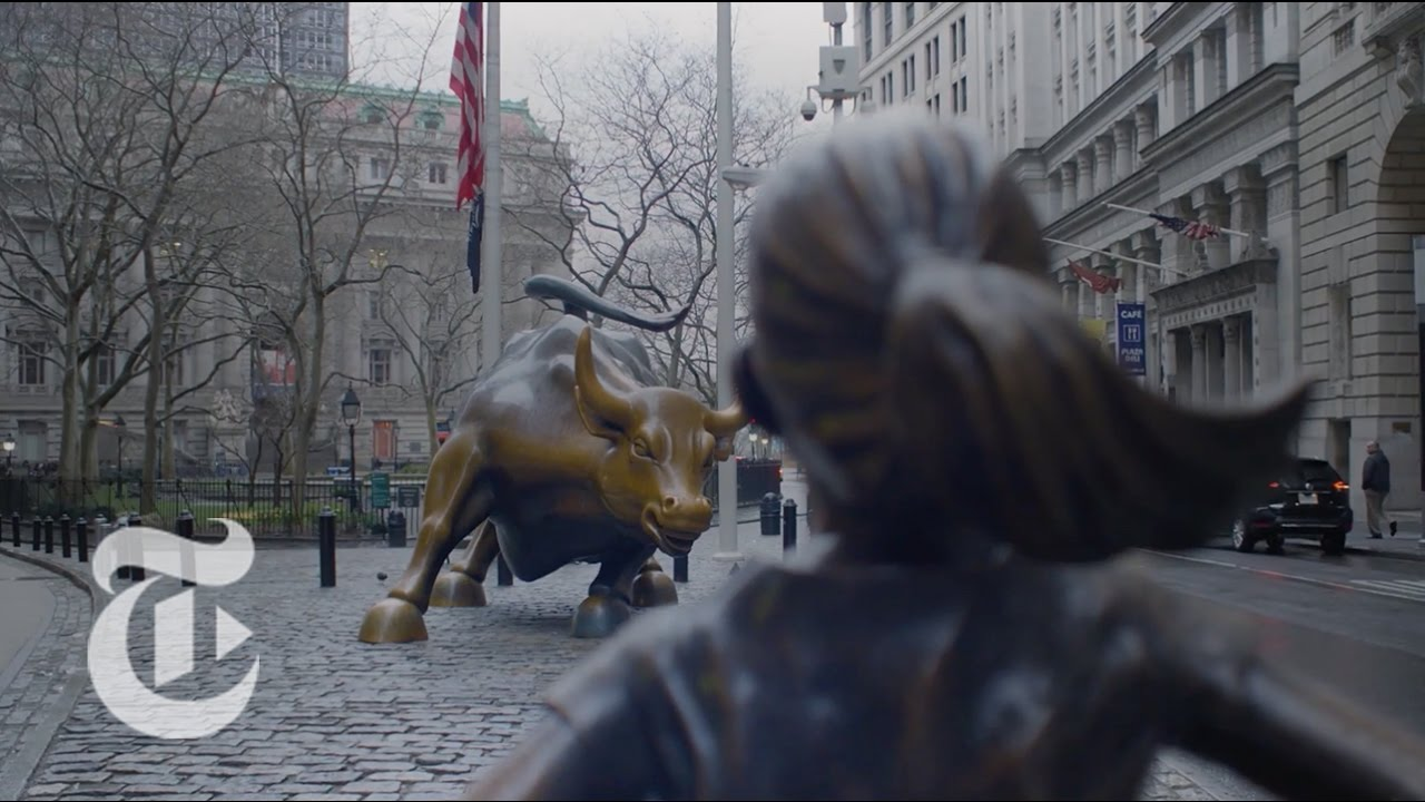 Wall Street Bull Art statue of courageous girl faces wall street bull | the new york