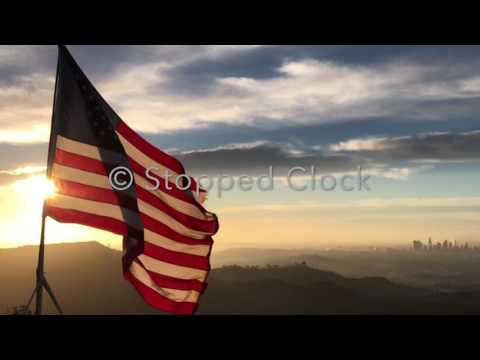STOCK FOOTAGE - American Flag Flying In The Wind At Sunrise Slow Motion