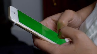 Girl using a cell phone with the green screen (tapping, scrolling, massaging)