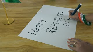 Tilt shot of woman hands writing 'Happy Republic Day' text on a festive card