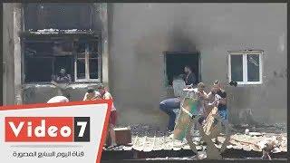 أهالى إمبابة يشاركون فى إخلال أحد المخازن المحترقة فى سوق الملابس