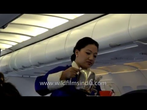 Bhutanese lady flight attendant and purser serve tea and coffee on board Druk Air
