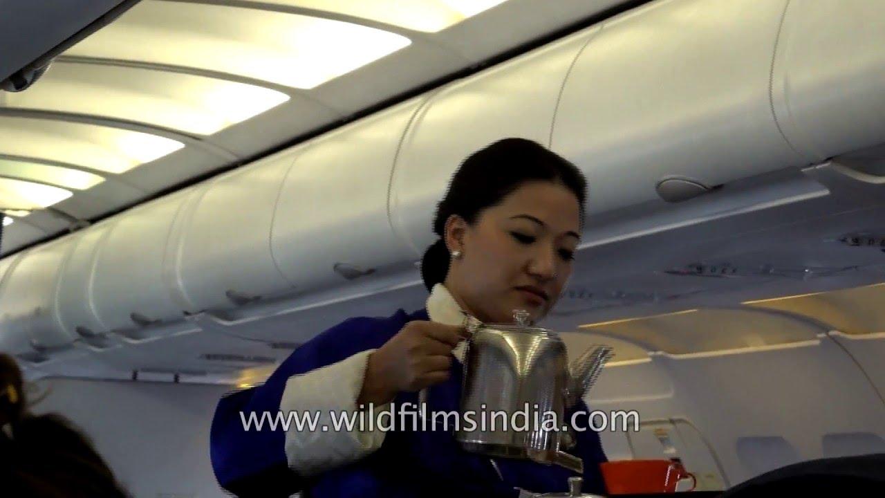 Bhutanese Lady Flight Attendant And Purser Serve Tea And Coffee On