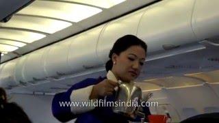 Bhutanese lady flight attendant and purser serve tea and coffee on board Druk Air