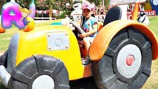 Anna play with a white toy elephant on an animal farm
