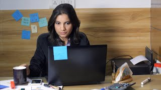 Indian girl working in office takes a sip of tea and makes weird facial expression