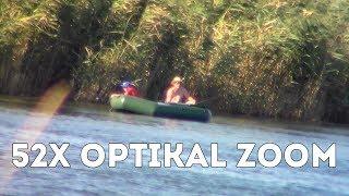 Папа с сыном ловят рыбу на резиновой лодке   съёмка издалека на видеокамеру с большим зумом
