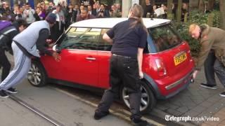 Group of men lift Mini blocking tram in Nottingham