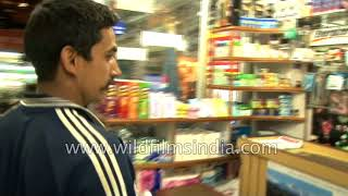 Indians shop for soda and nuts from a grocery shop in Nepal