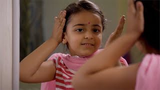 Cute little girl playing, dressing, looking in the mirror and putting a bindi on her forehead at home