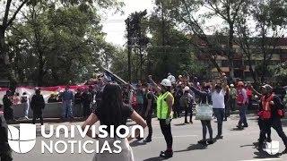 Para evitar el ruido estos voluntarios impiden el tránsito en una zona de rescate en México