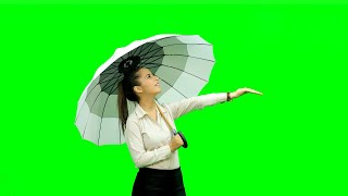 Cute girl standing with an umbrella and enjoying in rain against the green screen