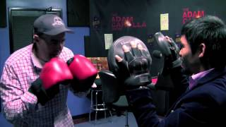Manny Pacquiao holds the focus pads for Adam Carolla