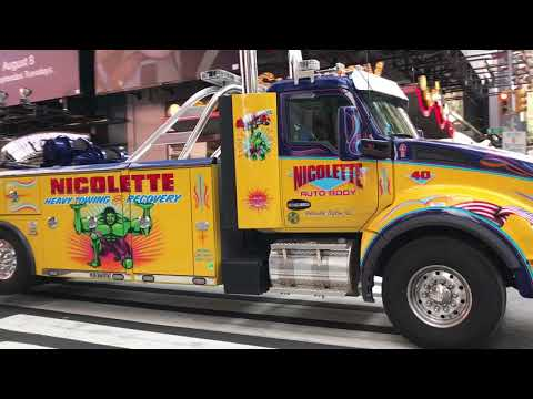 GIANT HEAVY WRECKER TOWING BROKEN DOWN POLAND SPRINGS TRUCK ON 42ND ST. IN TIMES SQUARE, MANHATTAN.