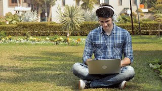 Young happy boy with headphones sitting in park and chatting on Laptop on a bright sunny day