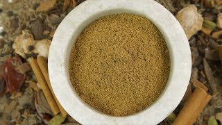 Aromatic garam masala powder in a stone bowl with the blend of raw spices in the background