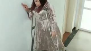 Beautiful oriental girl crutching on her polio legs.