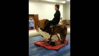 Linda riding the bull at the reception.