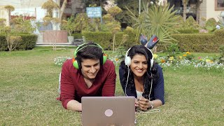 Young happy couple with headphones lying in a park and enjoying a movie on a laptop